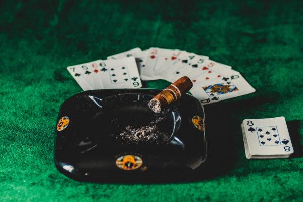 黒い灰皿の上に茶色いタバコ