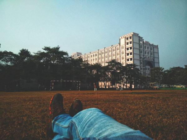 芝生のフィールドに横たわるデニムジーンズの足