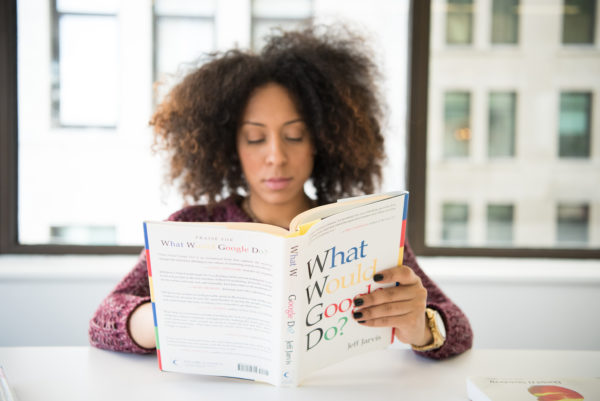 テーブルで本を読みながら座っている女性