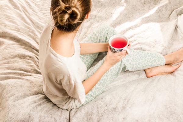 ベッドでお茶を飲む女性