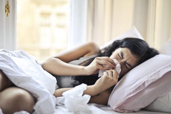 ベッドに横たわって鼻をかむ女性