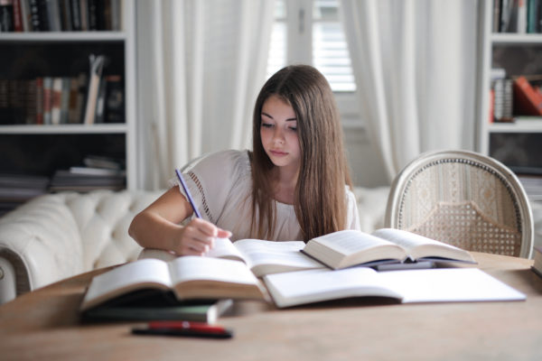 本を読んでいる灰色の長袖の女性