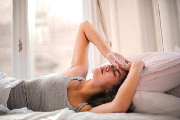 ベッドに横になっている灰色のタンクトップを着た女性