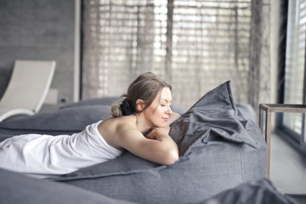 灰色のベッドに横たわっている白のタンクトップを着た女性