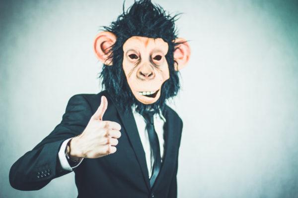 猿のかぶりものをしてスーツを着ている男