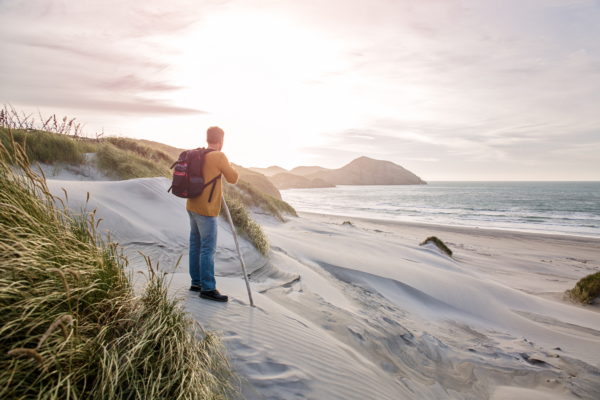 白い砂のビーチの上に立っている男