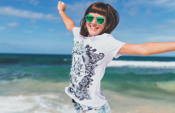 海岸で両手を上げながら笑みを浮かべている白と黒のシャツを着た女性