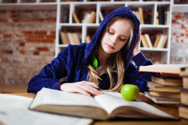 椅子に座ってテーブルの上で本を読んでいる青いジャケットを着ている女性