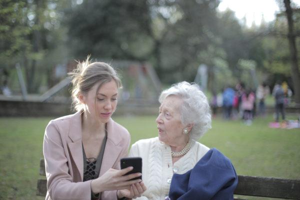 公園でスマートフォンを使用してシニアの母に教える大人の娘