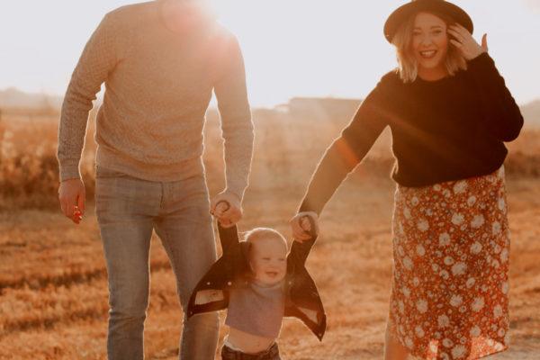 赤ん坊と手を繋いでいるカップルの写真