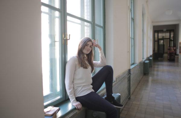 大学の廊下で座ってリラックスしている若い女性