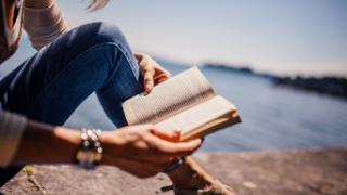 灰色のコンクリートの上に座って本を読む青いジーンズをはいた女性