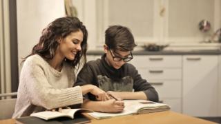 家で男の子に勉強を教えている成人女性